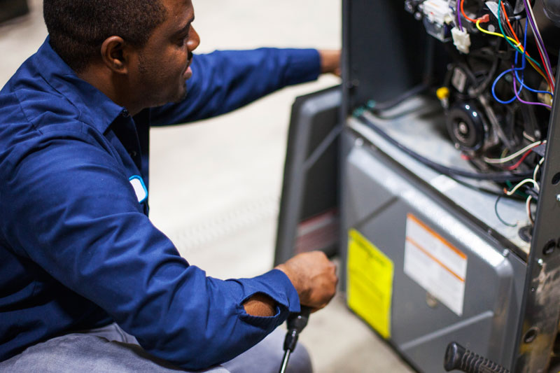 prosolutions furnace technician inspecting a high efficiency furnace during annual maintenance.
