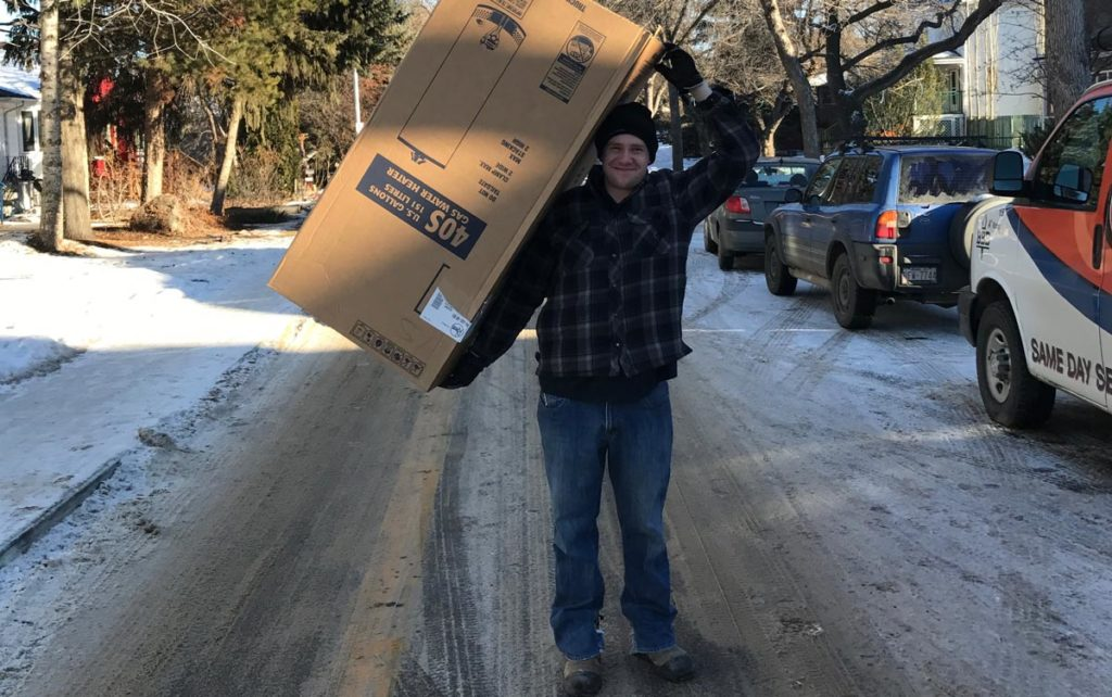 Edmonton man carrying a new amana furnace for replacement installation