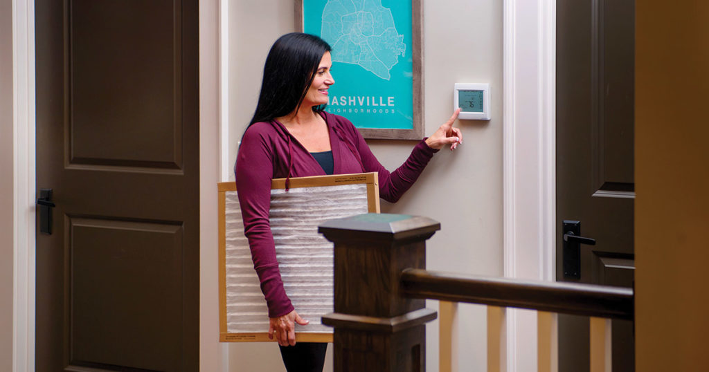 woman programming a new smart thermostat while holding a new furnace filter replacement